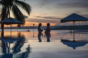 Honeymoon couple enjoying a cocktail while the sun sets at Iririki resort Vanuatu.